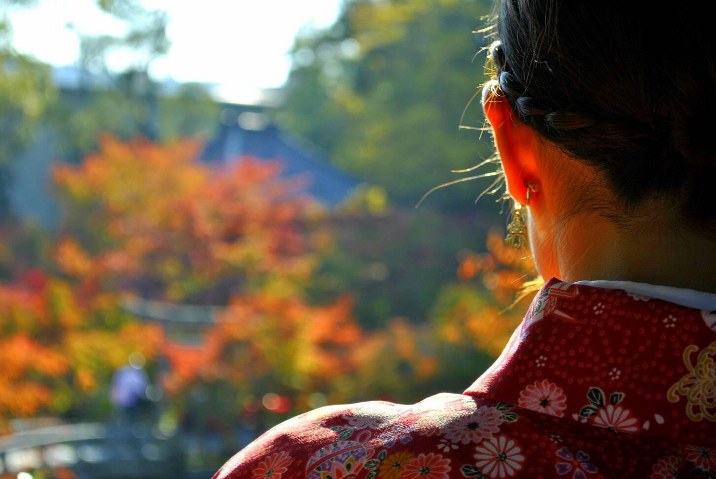 女性のうなじと紅葉の写真