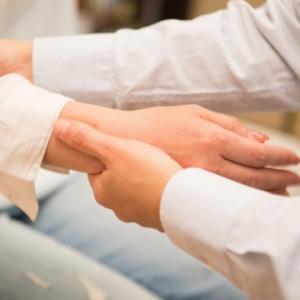 豊富な施術実績があります。患者さんの手を持って筋膜リリースをしている画像です。